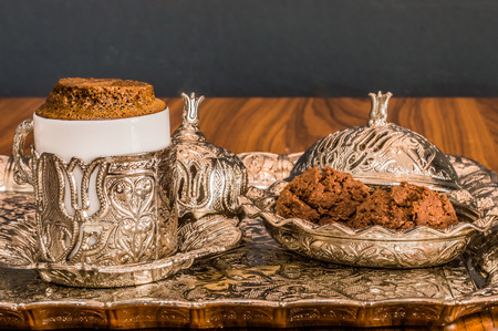 Turkish coffee served with cookies in a traditional copper serving set