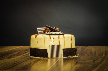 Delicious creamy whole white chocolate cake with chestnuts on top on a dark background Stock Photo