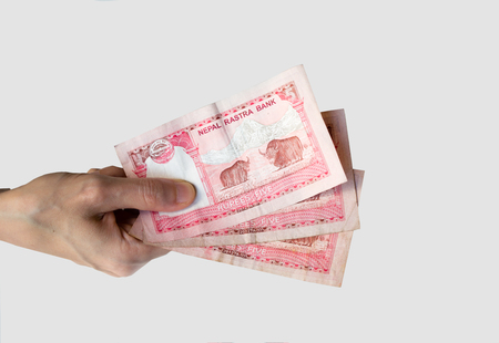 rupees: Woman holding fifteen Nepal Rupees banknotes in her hand