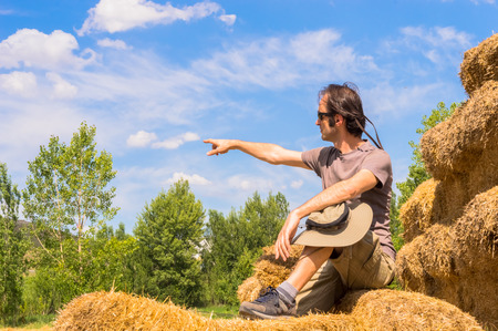 Handsome guy with hat sitting on straw bales and pointing his finger toward the blue sky. Stock Photo