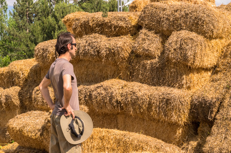 Handsome guy with hat standing with hands on his waist near straw bales.