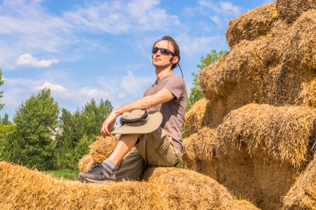 village man: Handsome guy with hat sitting on straw bales on a sunny day.