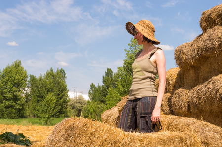 Pretty young woman with hat standing in straw bales and looking away on a sunny day.