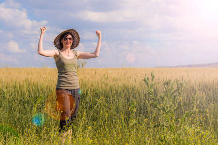 Caucasian woman with arms raised celebrating her success in a field on a summer day.
