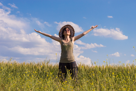 Young woman with hat standing on a field with her hands wide open. Stock Photo