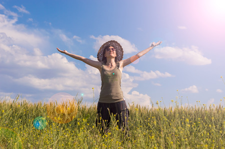Caucasian young girl with arms wide open feeling freedom  in green field on a sunny summer day. Stock Photo