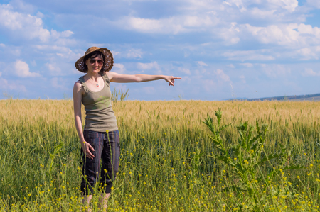 Caucasian woman  with hat pointing her finger toward the blue sky in a field. Stock Photo