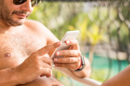 Half naked businessman using mobile phone while on the vacation