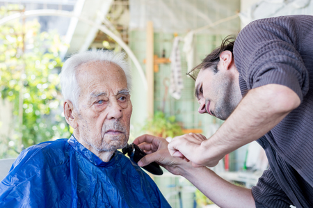 Elderly man getting his beard shaved by young skilled man at home