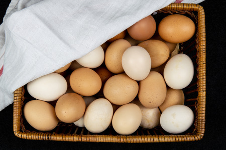 Top view of hen eggs in a basket on a black background Imagens
