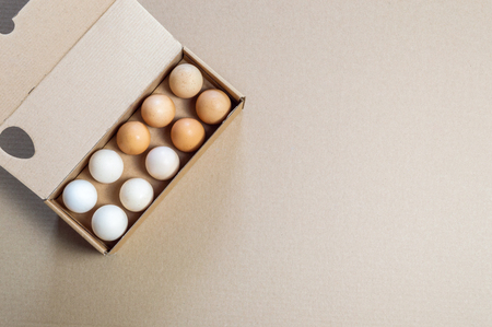Top view of carton egg container with fifteen eggs on a brown background. Stock Photo