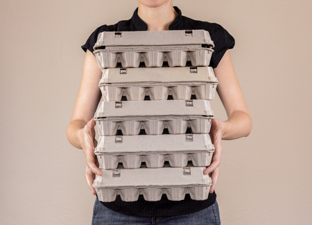 Caucasian woman with black shirt holding four cardboard egg boxes full of hen eggs.