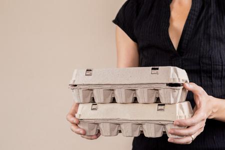 Caucasian woman with black shirt holding two cardboard egg boxes full of hen eggs. Reklamní fotografie