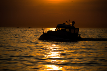Silhouette of a boat sailing on the Marmara sea at striking sunset. Stock fotó