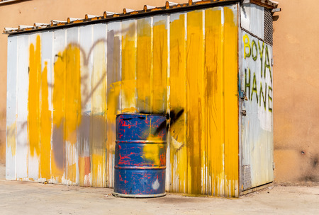 Blue metal drum in front of a shed painted in white and yellow with a text on the door: Dye house Stock Photo