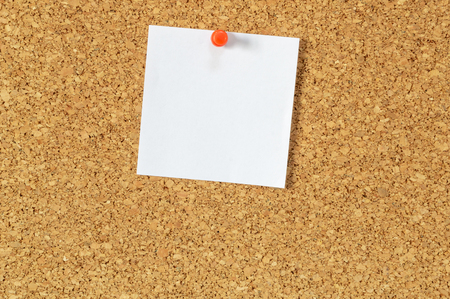 Cork board with pinned blank notepaper.