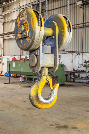 Closeup of a industrial yellow lifting crane hook in a factory.