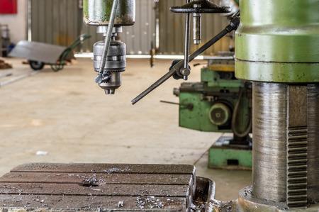 Industrial metal drilling tool in factory.