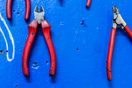Diagonal pliers on a  blue painted wooden board in a factory storage room. Stock Photo