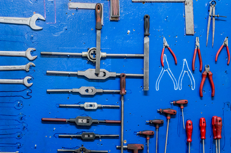 Working tools on blue painted wooden board in a factory storage room.