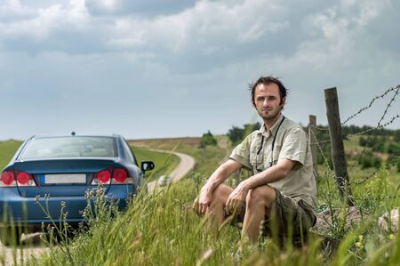 Caucasian man sitting in a rural area near his blue car on a cloudy spring day. Freedom concept. Stock Photo