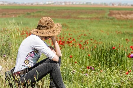 Young woman in casual clothing sitting in a meadow full of flowers. Nature concept.