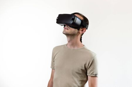 Caucasian man wearing shirt wearing virtual reality goggles on white background. Future technology concept. Stockfoto
