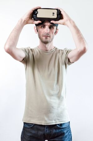 Caucasian man in t-shirt wearing virtual reality goggles on white background. Future technology concept.