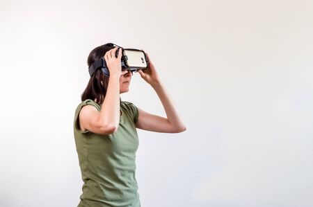 Caucasian woman with brown hair in green t-shirt wearing virtual reality goggles on white background. Future technology concept.