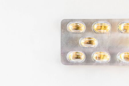 Top view of yellow capsules on white background. Medication concept.