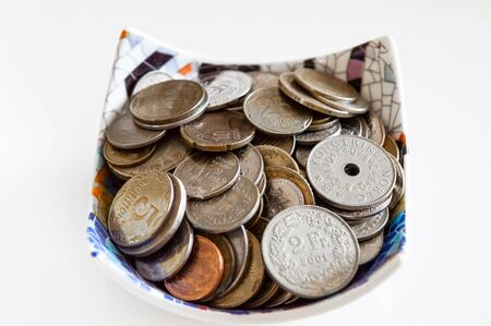 Bowl full of several coins from Ukraine, Switzerland and Norway on white background. Savings concept.