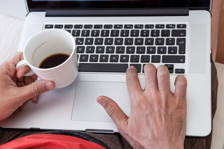 Young businessman holding mug of coffee while working on laptop computer on a couch at home. Portable office concept. Stockfoto