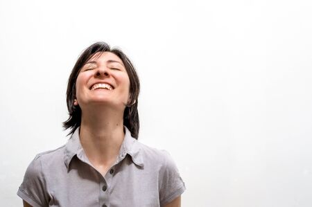 Portrait of a young happy brunette woman standing on a white wall, smiling with closed eyes in a peaceful manner. Stok Fotoğraf