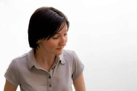 Portrait of a pretty young brunette woman looking down or watching something against a white wall.