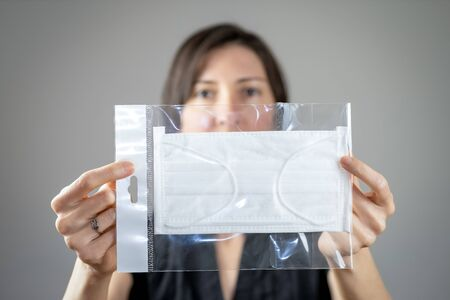 Adult woman holding hygienic mask in package for infection awareness, airborne respiratory illness such as flu, 2019-nCoV on gray background. Healthcare concept.