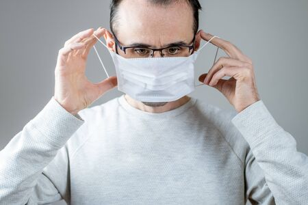 Adult man wearing hygienic mask to prevent infection, airborne respiratory illness such as flu, 2019-nCoV on gray background. Healthcare concept.