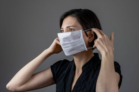 Brunette woman wearing hygienic mask to prevent infection, airborne respiratory illness such as flu, 2019-nCoV on gray background. Healthcare concept. Stok Fotoğraf
