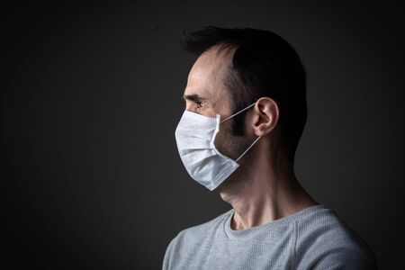 Adult man wearing hygienic mask to prevent infection, airborne respiratory illness such as flu