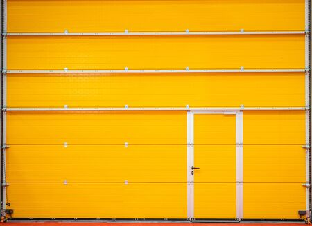 Yellow closed coiling door or roll-up of a hangar. Yellow steel, rolling shutter door texture with horizontal lines. Banque d'images - 144296076