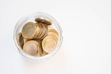 Top view of 1 Turkish Lira (TRY) coins in a jar on isolated on white background. Money growth and deposit accumulation concept.