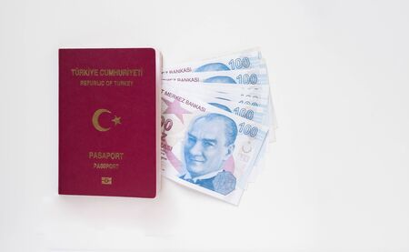 Turkish passport and a bunch of 100 Turkish Lira (TRY) banknotes isolated on white background. Money and travel concept. Stok Fotoğraf