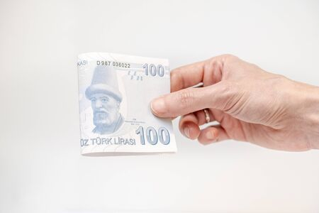 Female hand holding a 100 Turkish Lira (TRY) banknote isolated on white background.