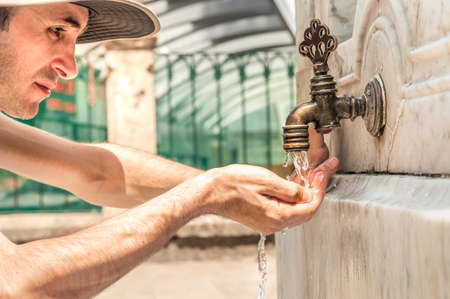 Young man drinking water with his hand from an antique Turkish fountain on a marble wall. Water running from the faucet.
