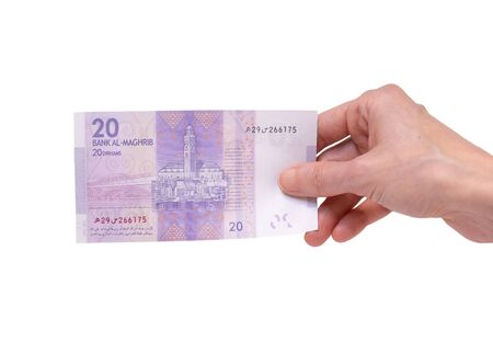 Female hand holding a 20  Moroccon Dirham banknote isolated on a white background. Denomination of 20 Dirhams.