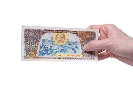 Female hand holding a 500 Kip 1988 banknote currency isolated on a white background. Denomination of 500 Kips.
