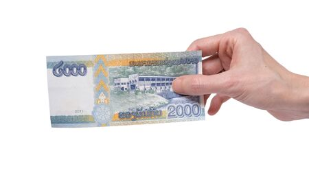 Female hand holding a 2000 Kip banknote currency isolated on a white background. Denomination of 2000 Kips.