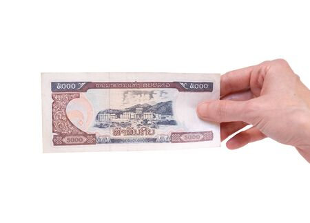 Female hand holding a 5000 Kip banknote currency isolated on a white background. Denomination of 5000 Kips.
