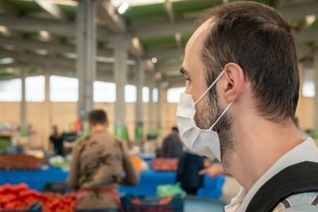 Portrait of a Turkish brunet man wearing medical mask at traditional grocery bazaar during coronavirus days in Eskisehir, Turkey. Stok Fotoğraf