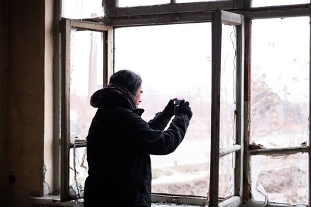 Adult man with black cold winter coat taking pictures of the outside view from the broken window of an abondened house on a cold winter day.
