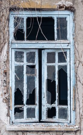 Windows of an abandoned building with wooden frames and broken glasses. Stok Fotoğraf